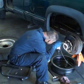Technician installing a wheel on a vehicle
